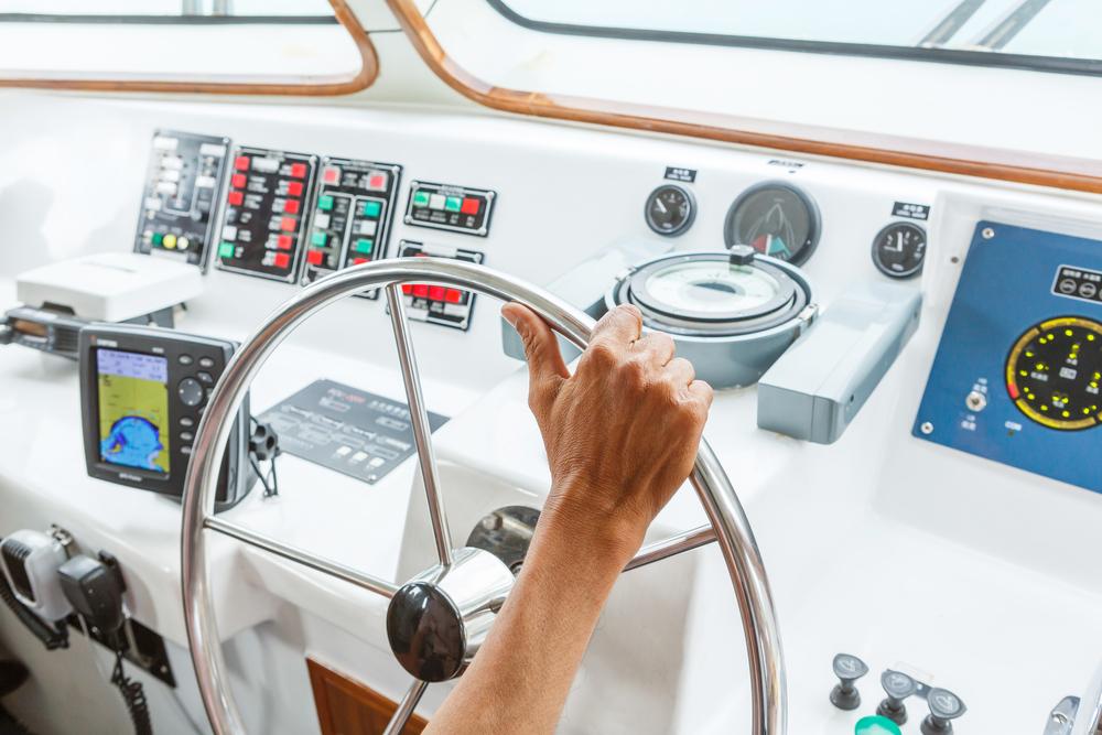 man on steering wheel of yacht