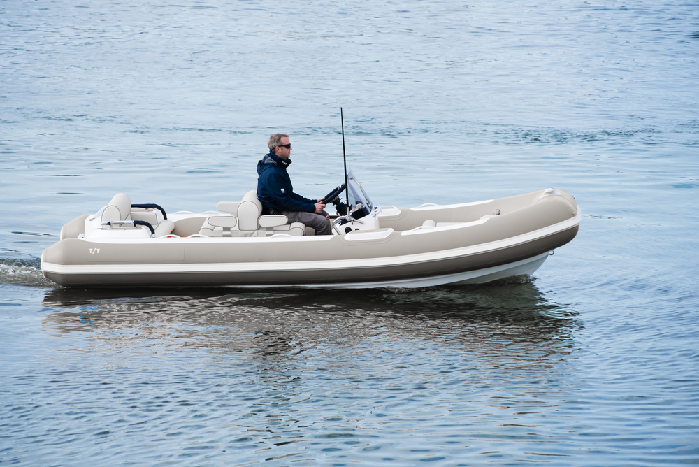 man driving tender boat for yacht